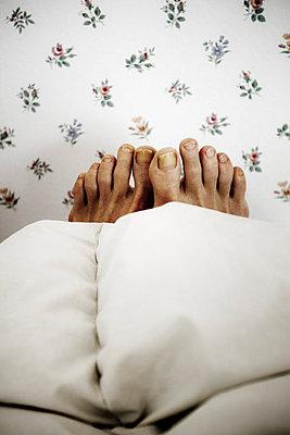 A pair of feet sticking out from under the covers in bed (Ett par fötter sticker fram under täcket i säng ) - p847m673086 by Anna Molander