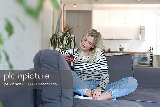 Junge Frau mit Smartphone auf dem Sofa - p1301m1582588 von Delia Baum