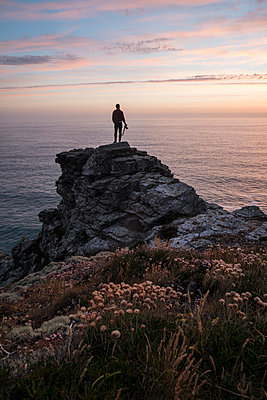 Rear view of silhouette man standing on cliff at beach against sky during sunset - p1166m1521146 by Cavan Images