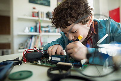 Focused boy assembling circuit board - p1192m1129530f by Hero Images
