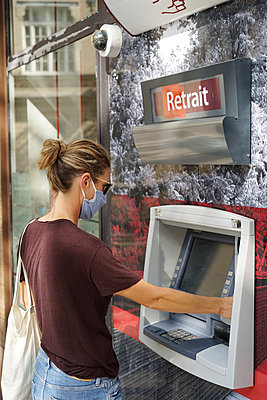 A woman wearing a cloth protective mask withdraws money at a cash machine - p1610m2209942 by myriam tirler