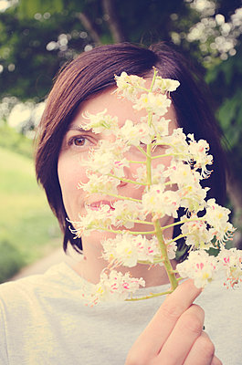 Woman holding flower in front of face - p577m1564755 by Mihaela Ninic