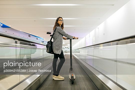 Businesswoman with her electric scooter on moving walkway - p300m2155389 by Josep Rovirosa
