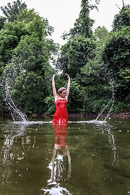 Girl In Red Dress in Stream - p1019m2100433 by Stephen Carroll