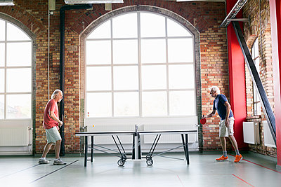 Full length side view of senior men playing table tennis in fitness club - p1185m994325f by Astrakan