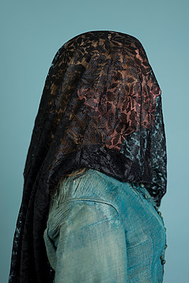 Profile of woman in original Victorian dress with head covered in black lace. - p1433m1586197 by Wolf Kettler