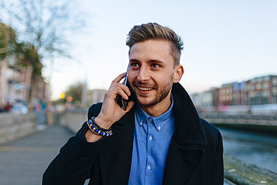 Ireland, Dublin, portrait of young businessman telephoning with smartphone - p300m1101028f by Boy photography