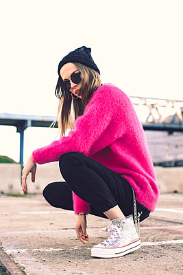 Portrait of fashionable young woman wearing sunglasses, cap and pink knit pullover - p300m2078767 by Aitor Carrera Porté