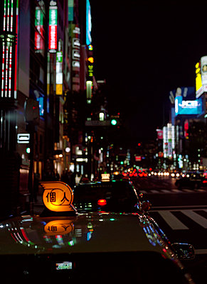 Street scene at night in Ginza district with taxi and street lights, Tokyo - p3490025 by Brent Darby