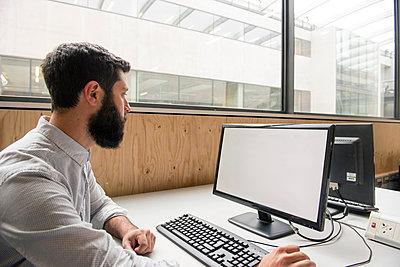 Man in office using desktop computer - p429m1513875 by G. Mazzarini