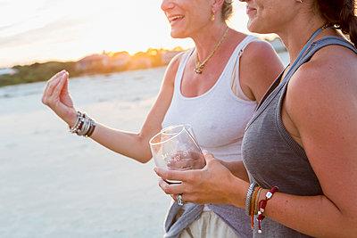Caucasian women drinking wine on beach - p555m1522763 by Marc Romanelli