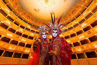 A couple in red costumes and masks pose in the Fenice theatre during the Venice Carnival, Venice, Italy - p651m2033945 by Tim Mannakee