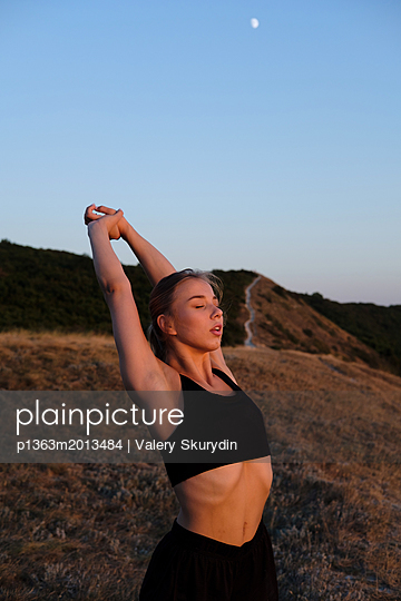 Athletic young woman is stretching and training outdoor on grass