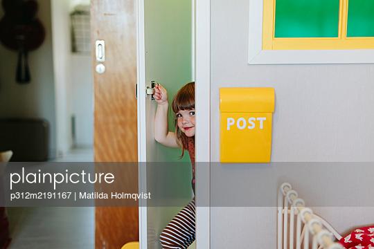 Girl peeking through door - p312m2191167 by Matilda Holmqvist
