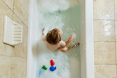 Overhead view of boy playing in bathtub - p1166m1210618 by Cavan Images
