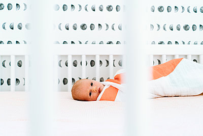 Closeup portrait of a newborn baby girl laying in a modern crib - p1166m2171911 by Cavan Images