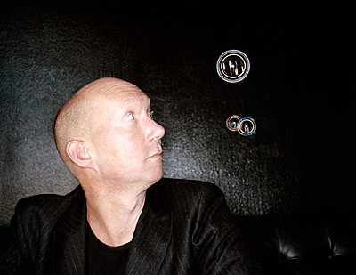 Bald man looking at soap bubbles  - p1207m1109474 by Michael Heissner