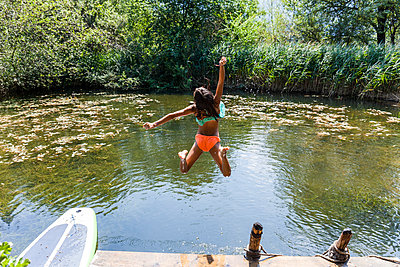 Carefree girl jumping into pond - p300m2030522 by Tom Chance
