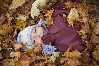 High angle view of a girl lying in a pile of leaves - p3487041 by Tomas Holmqvist
