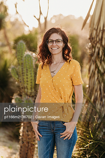 Headshot of young mother wearing glasses in backlight cactus garden - p1166m2136702 by Cavan Images