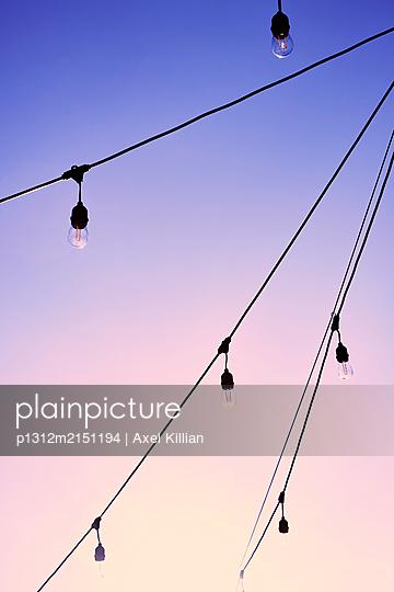 Fairy lights with light bulbs against sky - p1312m2151194 by Axel Killian