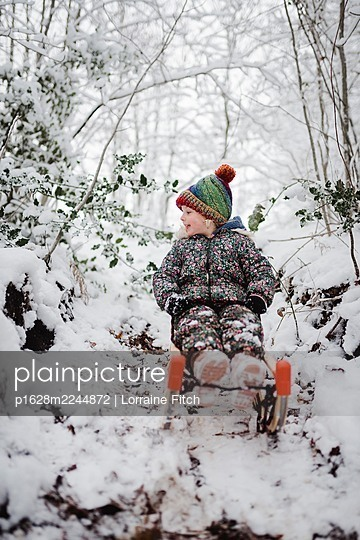 LIttle girl on a sledge in the snow - p1628m2244872 by Lorraine Fitch
