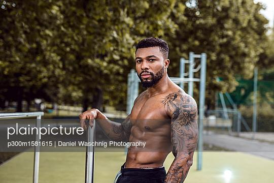 Portrait of tattooed physical athlete  on sports field - p300m1581615 von Daniel Waschnig Photography