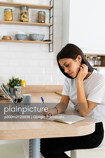 Young woman with laptop taking notes at home - p300m2120036 by Giorgio Fochesato