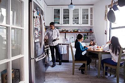 Family having breakfast in kitchen - p1166m1211414 by Cavan Images