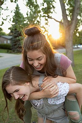 Playful teenage girl friends piggybacking in park - p1192m2016954 by Hero Images