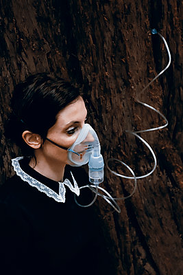 Woman with oxygen mask plugging into a tree - p1521m2228347 by Charlotte Zobel