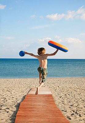Boy (8-9) running down boardwalk to sea - p42913446f by Ashley Jouhar