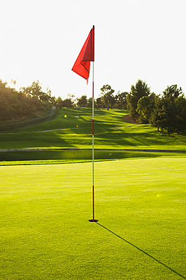 Flag in hole on golf course - p555m1311580 by PBNJ Productions
