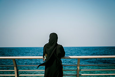 Rear view of a Muslim woman standing by the sea  - p794m1538518 by Mohamad Itani