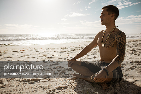 Man practises meditation on the beach in the sunshine - p1640m2261020 by Holly & John