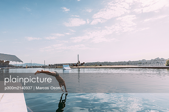 Young man jumping into water from a pier - p300m2140937 by Marcos Osorio