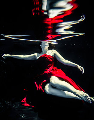 Woman in red dress floating underwater - p1019m1461905 by Stephen Carroll