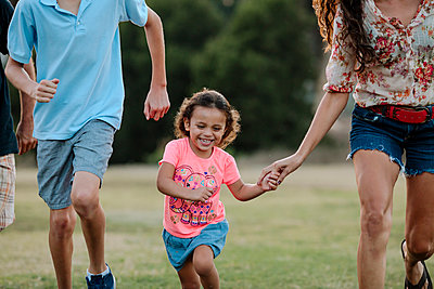 Playful family running at park - p1166m1530905 by Cavan Images