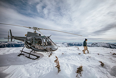 Helicopter pilot explores a snow-covered mountain summit. - p1166m2137120 by Cavan Images