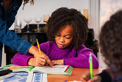 Cropped hand of mother assisting daughter studying at home - p1166m2163273 by Cavan Images