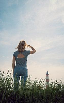 Frau schaut auf den Westerheversand Leuchturm - p1443m2185147 von SIMON SPITZNAGEL
