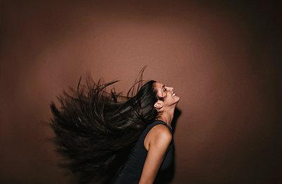 Junge Frau schüttelt ihre langen dunklen Haare - p586m953771 von Kniel Synnatzschke