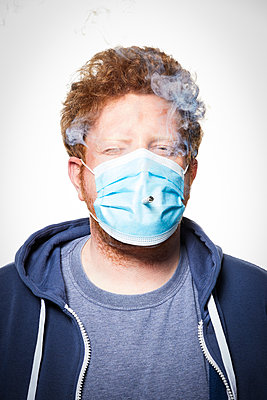 Man with surgical mask and cigarette, portrait - p930m2253775 by Ignatio Bravo