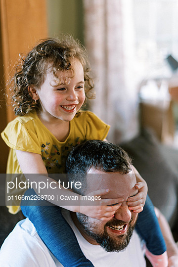 A father playing with his daughter on his shoulders in living room - p1166m2269700 by Cavan Images