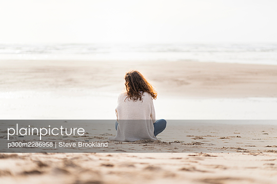 Woman looking at view while sitting on sand during vacations - p300m2286958 by Steve Brookland