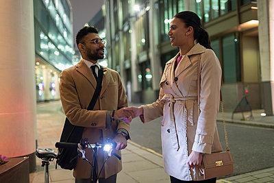 Business people with bicycle handshaking on urban sidewalk at night - p1023m2017047 by Paul Bradbury