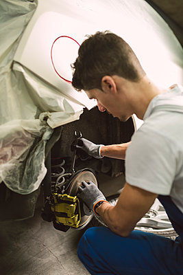 Mechanic fixing the brake caliper of a car in a workshop - p300m1587344 von Ramon Espelt