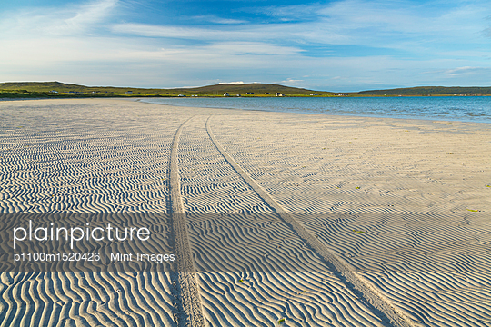 Vehicle tracks along a sandy beach with ocean and hills in the distance. - p1100m1520426 by Mint Images