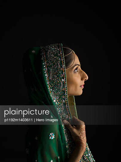 Profile portrait serious Indian woman wearing headscarf and looking up against black background - p1192m1403611 by Hero Images