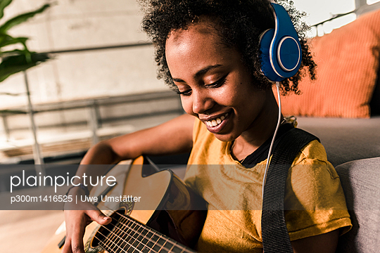 Smiling young woman at home with headphones playing guitar - p300m1416525 by Uwe Umstätter